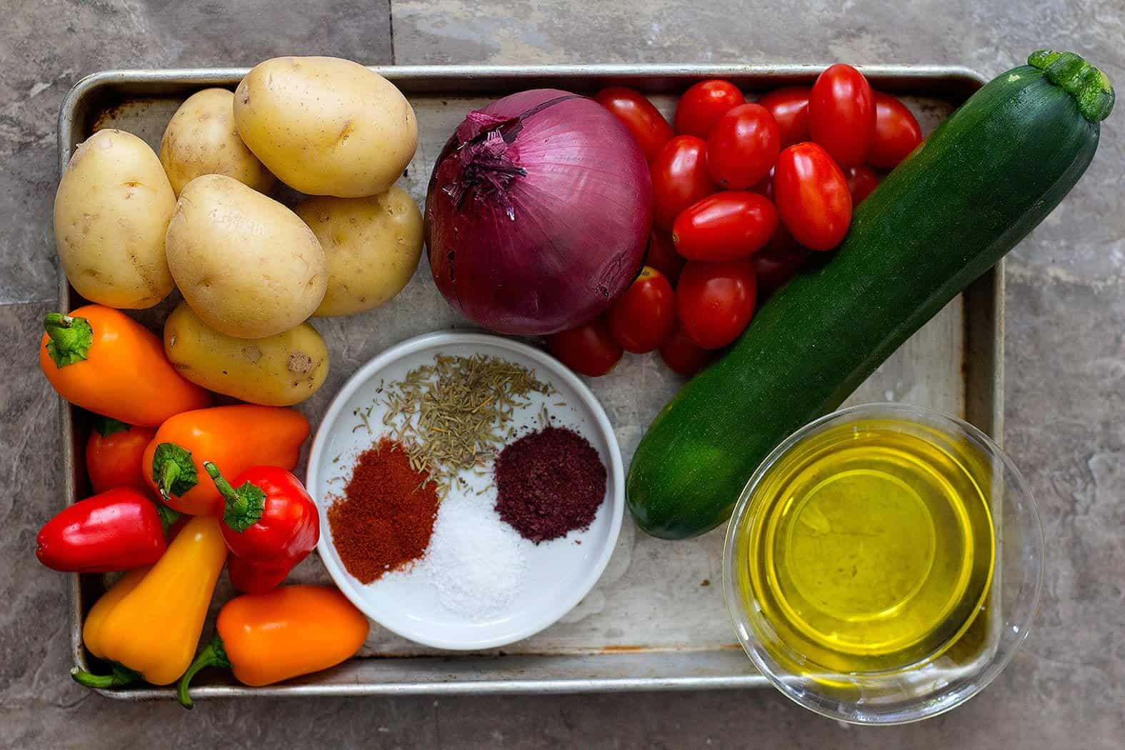 Use pepper, potatoes, onion, tomatoes, zucchini, olive oil and spices to make roasted vegetables in oven.