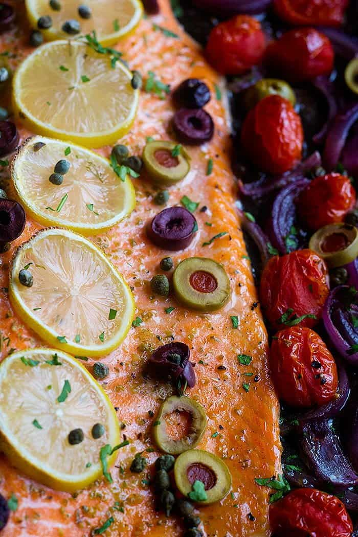 The best ever oven baked salmon is here! Flaky and moist Alaska salmon with olives and capers on a bed of vegetables is an outstanding choice for your weeknight dinner.