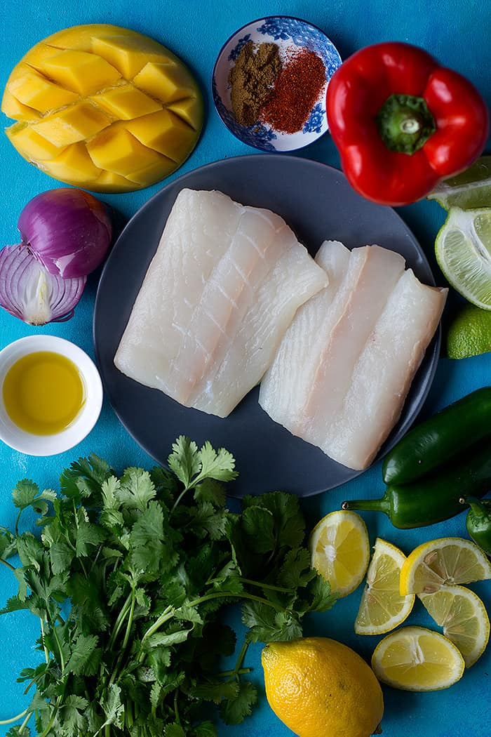 To make grilled halibut you need halibut, mango, cilantro, red onion, olive oil, peppers, lemon and lime