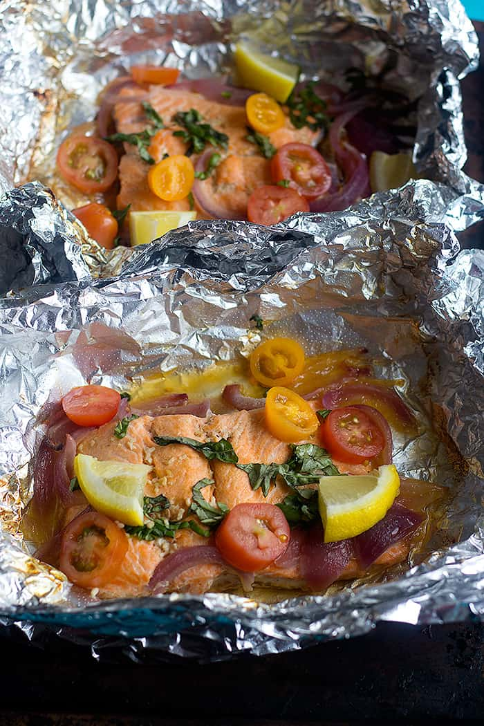 two salmon packets with basil, onion, lemon and tomatoes.