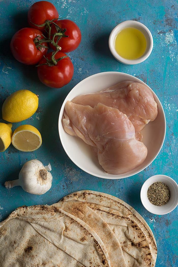 To make chicken souvlaki you need chicken lemon olive oil oregano and pitas and tomatoes.