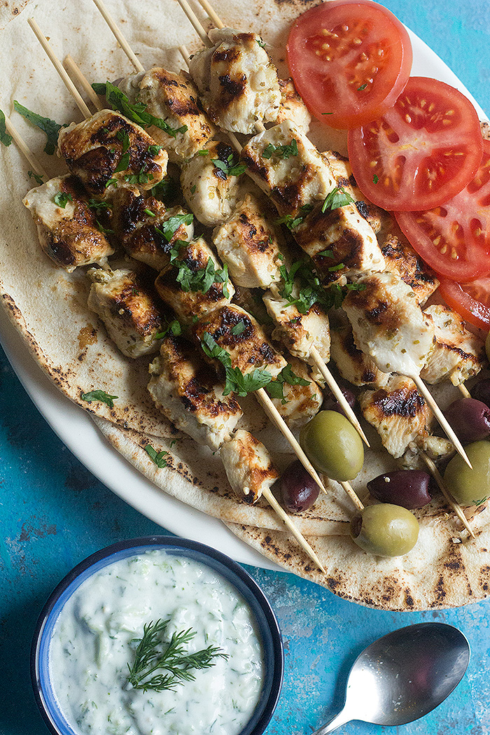 A delicious recipe for homemade chicken souvlaki made with an easy marinade and all the pita fixings. This Greek street food is packed with amazing flavors and is served with creamy tzatziki sauce.