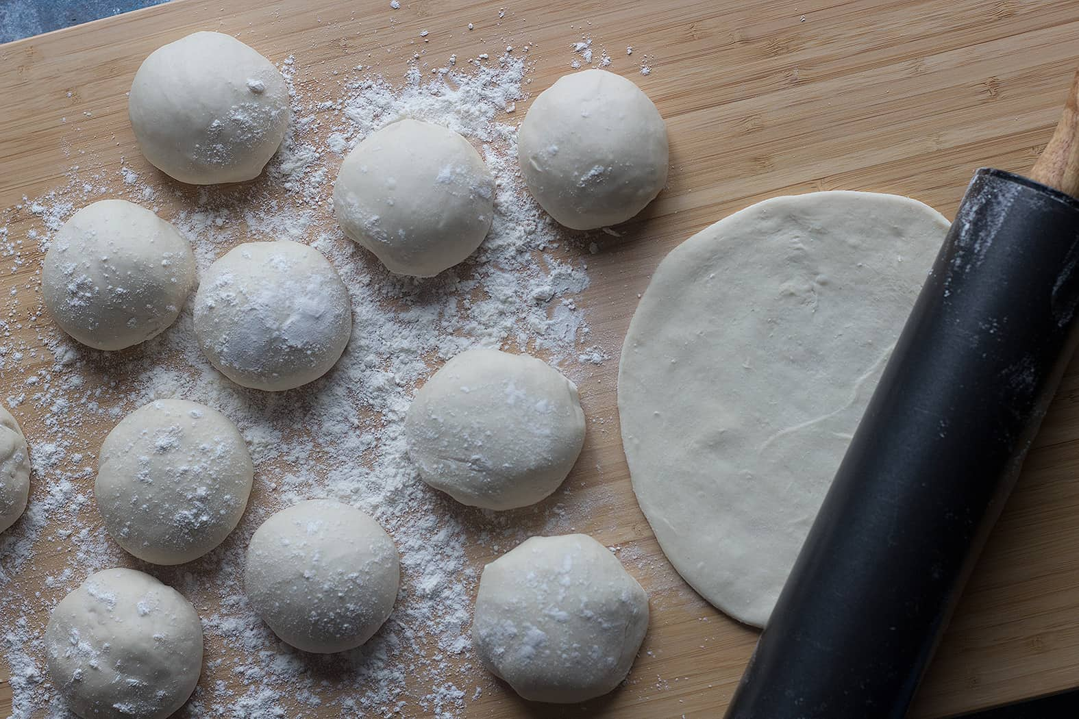 Divide Lahmacun dough into 12 balls and roll our very thin.