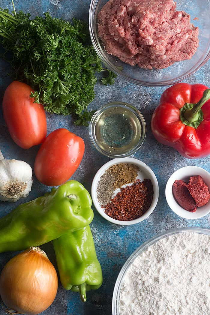 To make Lahmacun Turkish Pizza you need a dough and ground lamb or beef (or a combination of both), tomatoes, onions, garlic, parsley, red bell peppers andItalian green peppers. This mixture is seasoned with Aleppo pepper, tomato paste, black pepper and salt.