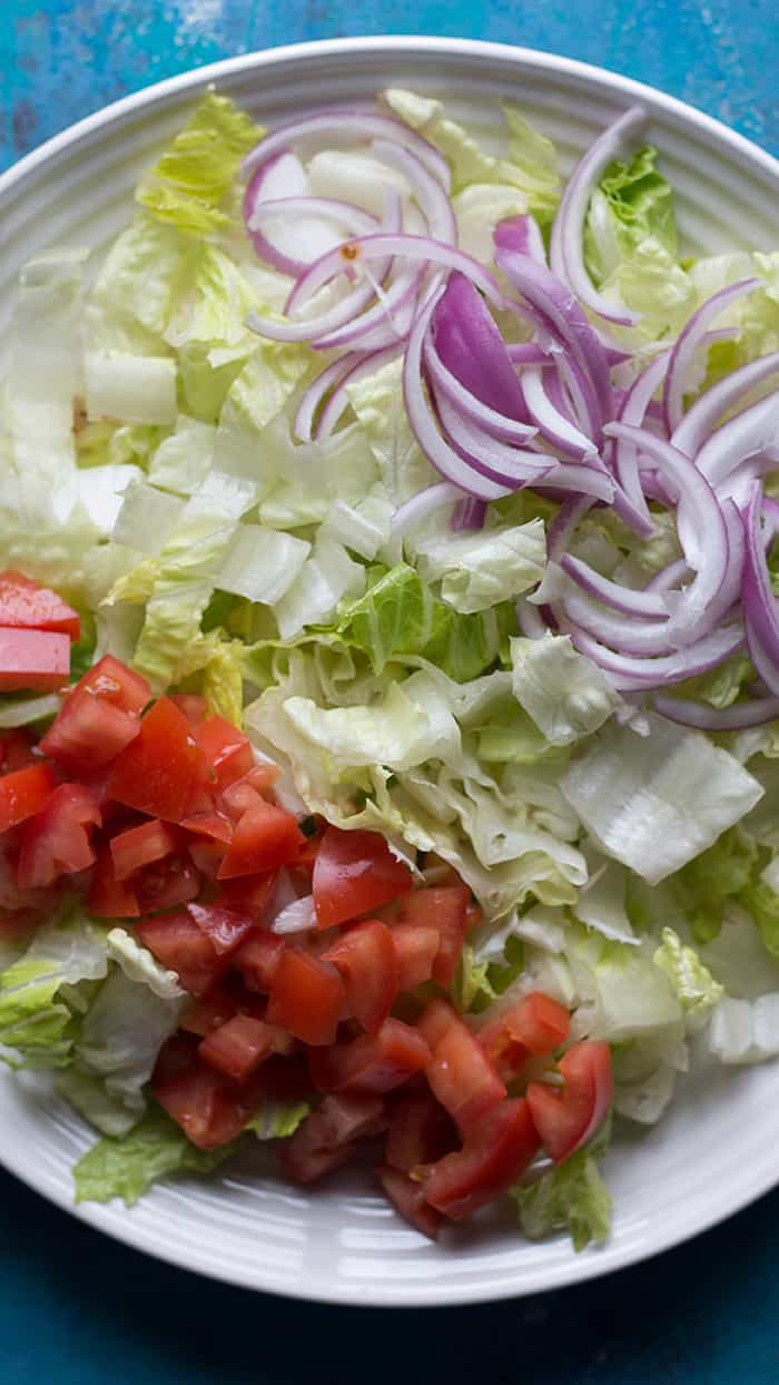 lettuce, onion and tomatoes ready on the plate.