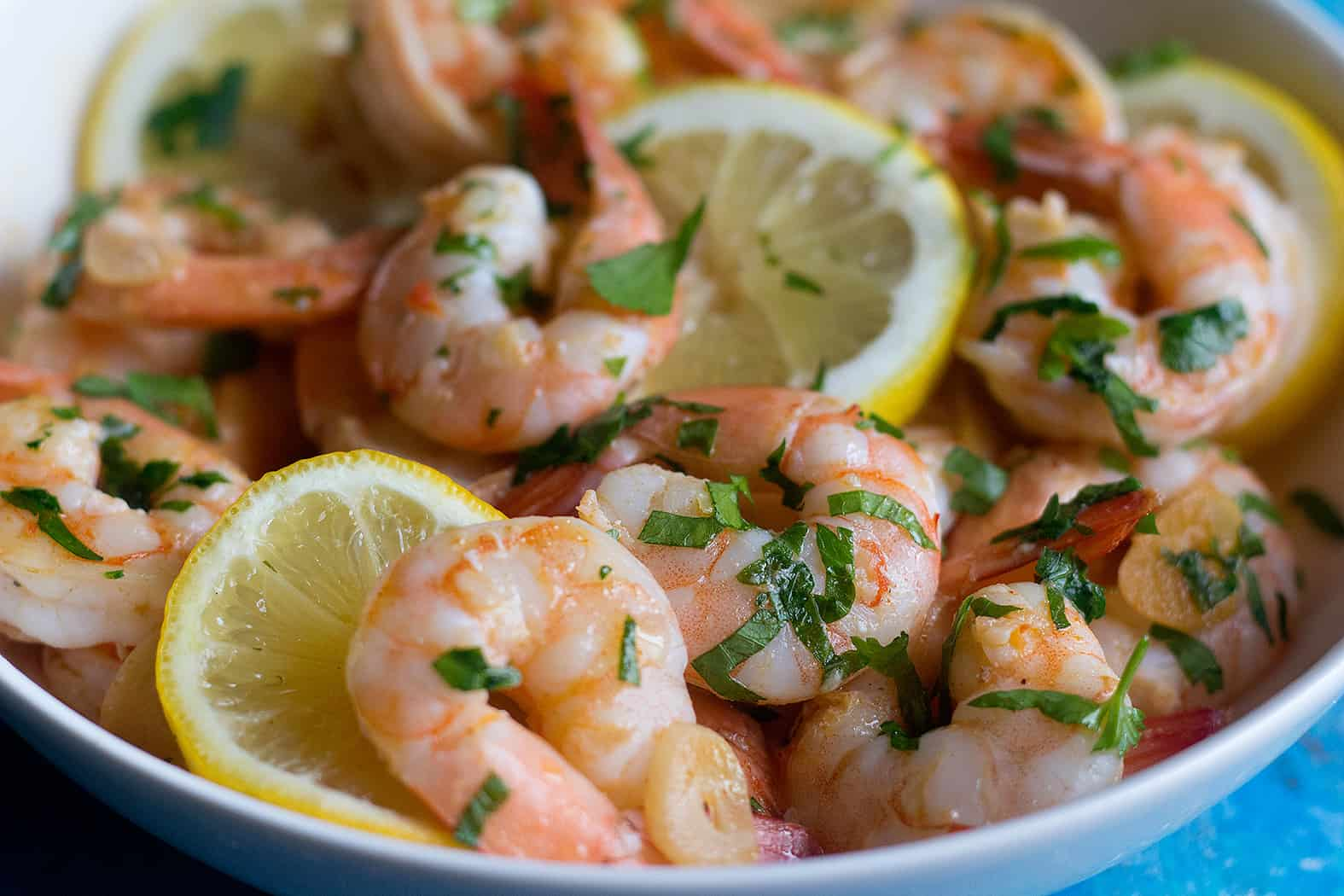 A bowl of sauteed shrimp served with lemon slices.