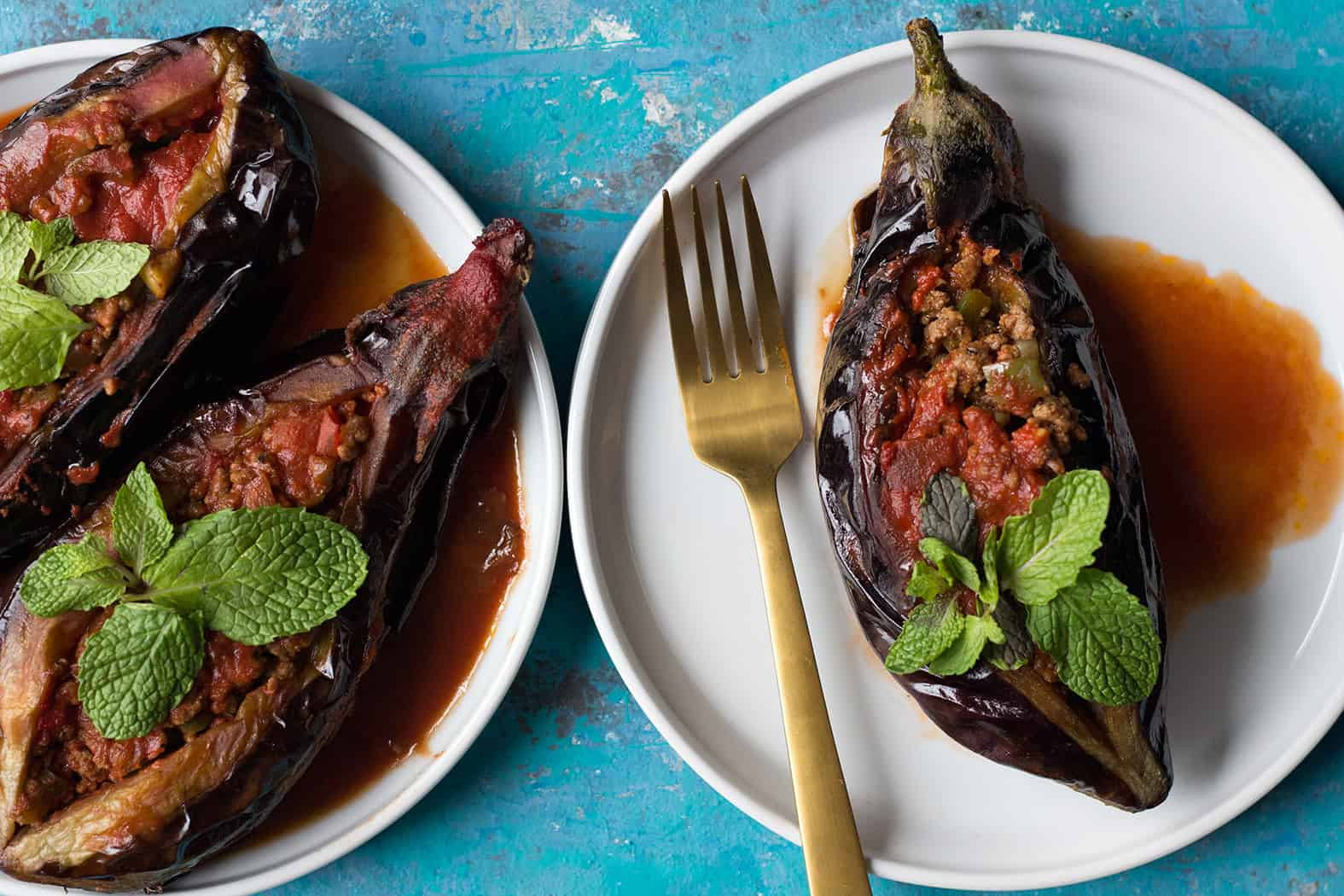 Turkish stuffed eggplant on white plates topped with fresh mint.