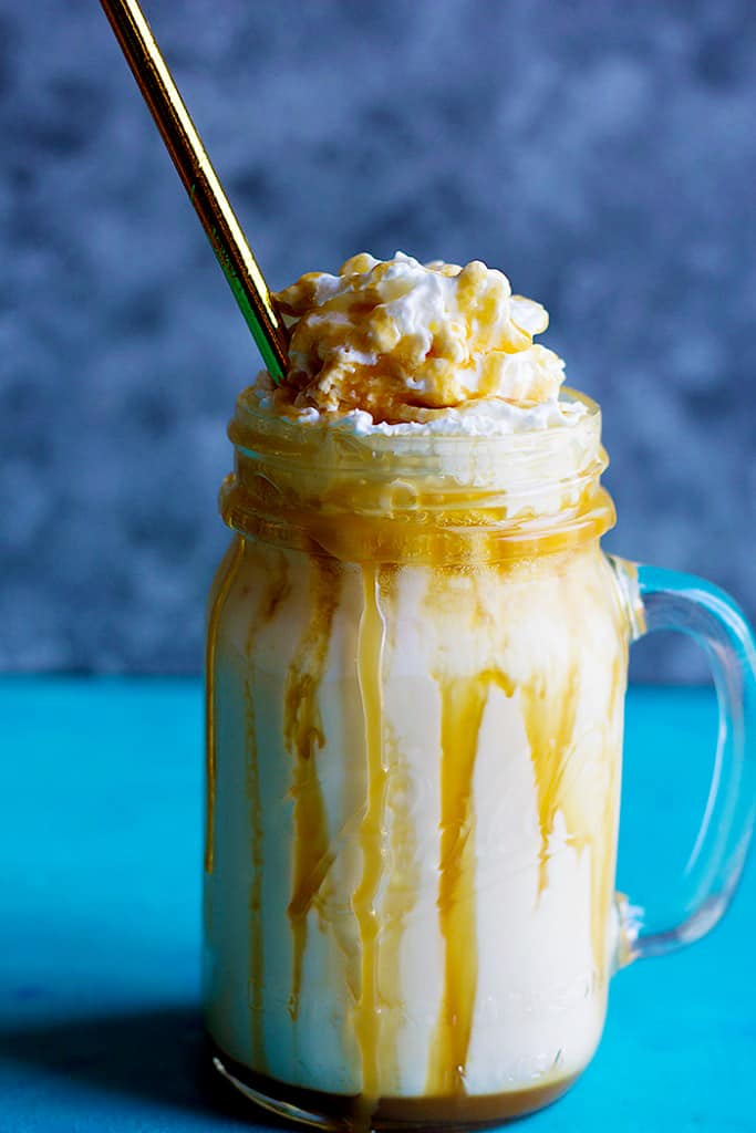 A glass of caramel milkshake with whipped cream and a golden straw.