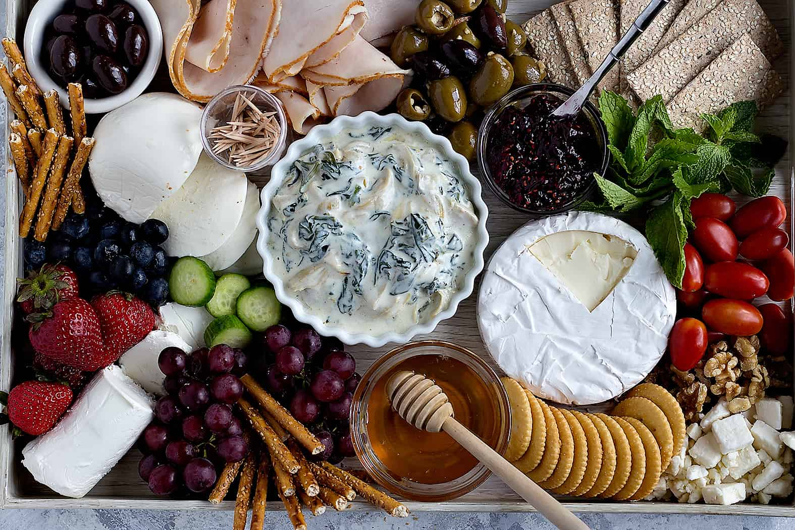 A large and beautiful charcuterie board with cheese, olives, fruit, meat and veggies