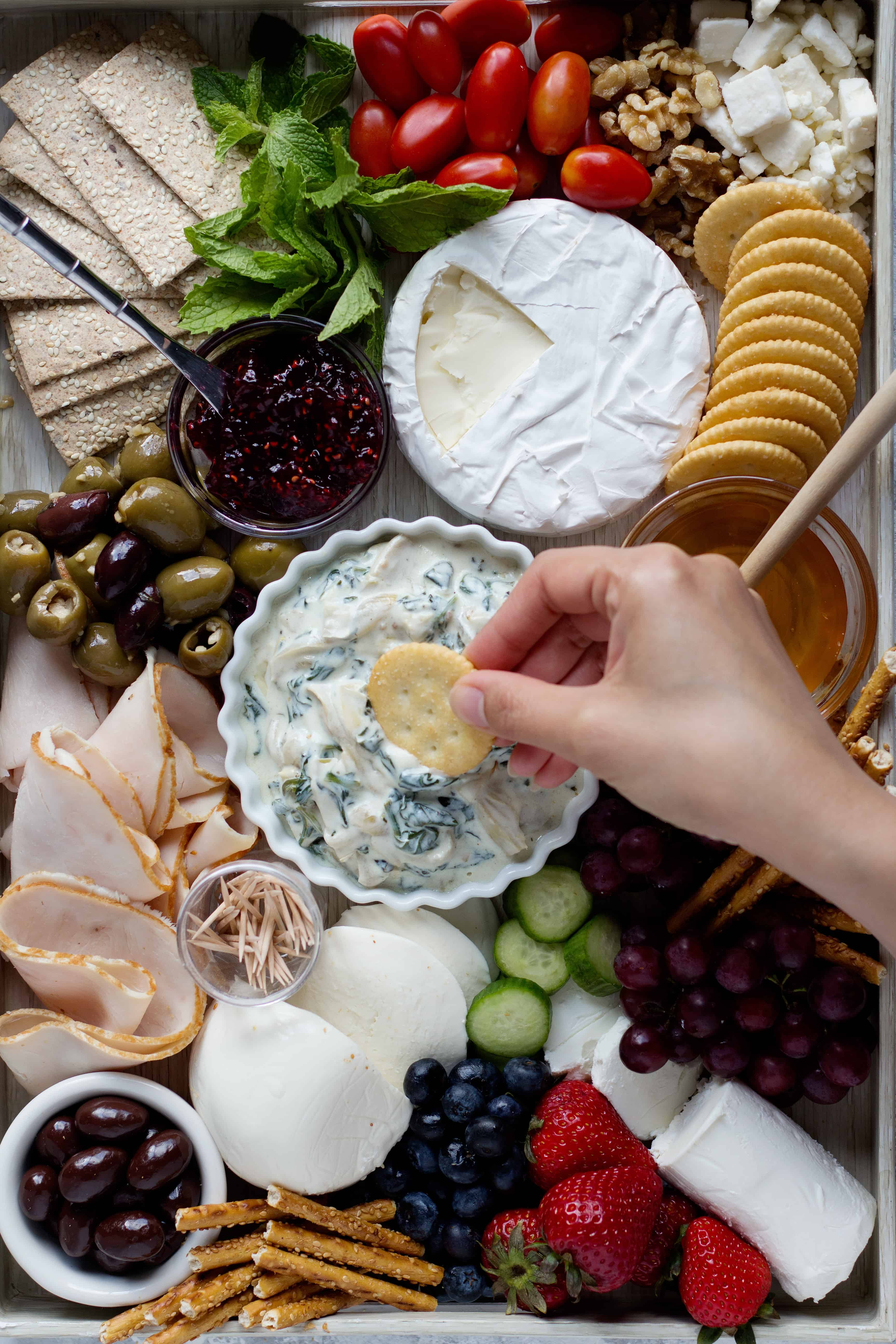 Dip crackers into a spinach artichoke dip with some olives and cheese.