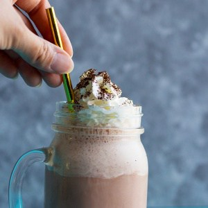 milkshake made with coffee in a glass with a golden straw