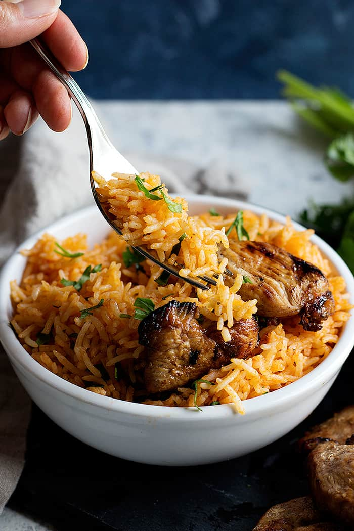 A bowl of Mexican rice with grilled chicken.