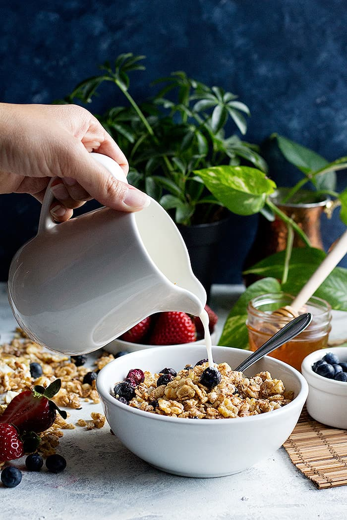 milk pour into the cereal with a background of plants and fruit.