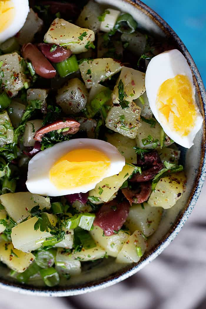 bowl of salad made with potatoes, eggs, herbs and olives