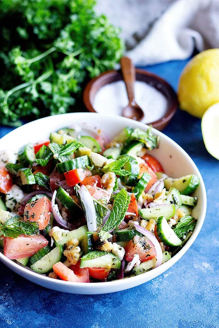 A bowl of tomato feta salad with fresh mints and salt and lemon.