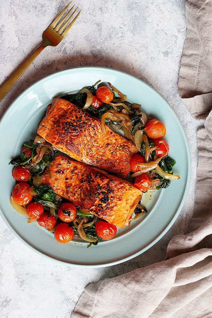 overhead shot of two salmon fillets with tomatoes and spinach.
