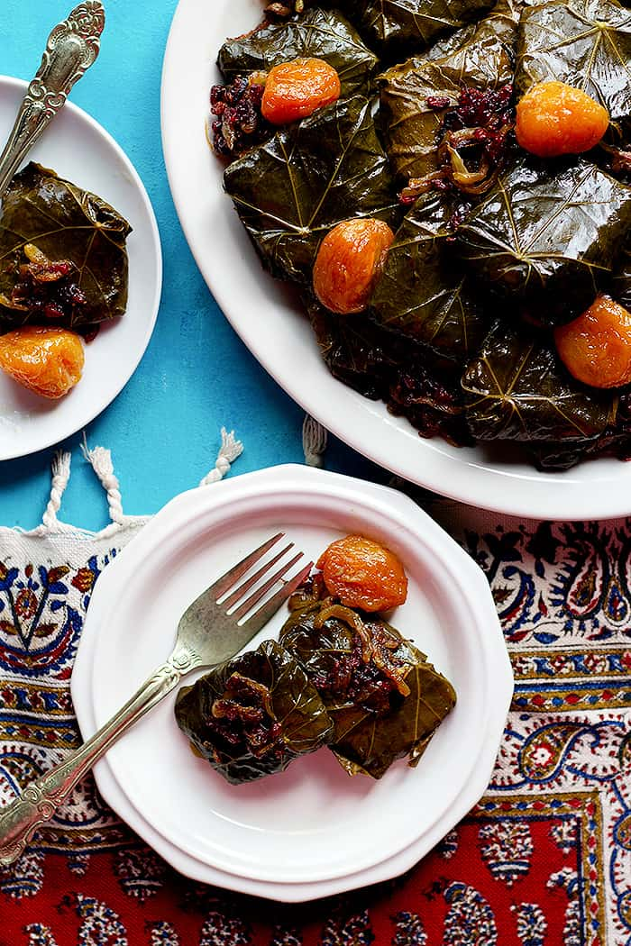 stuffed grape leaves made Persian style served on three plates.