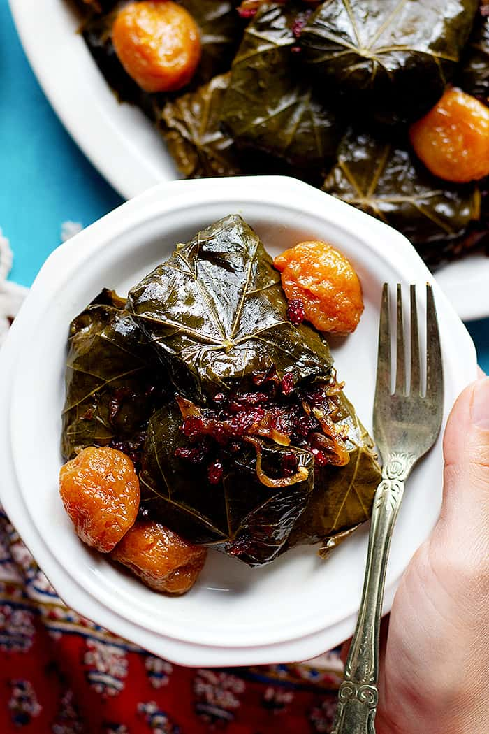 a plate of Persian stuffed vine leaves with onion, barberries and plums.