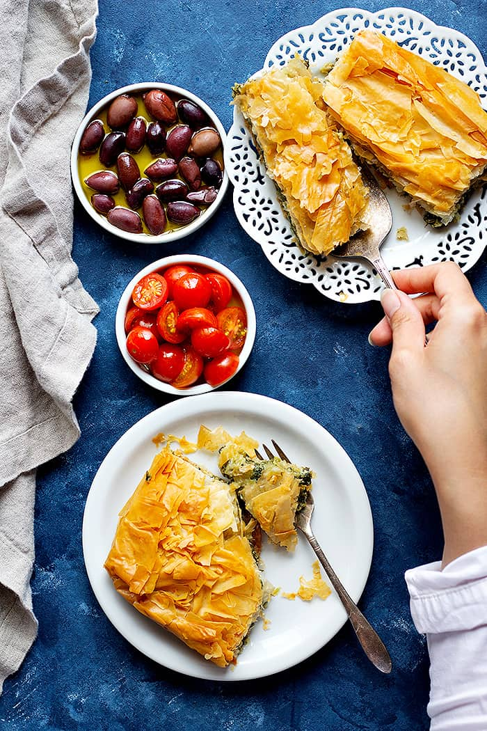 Greek spinach pie cut into slices and served with tomatoes and olives.