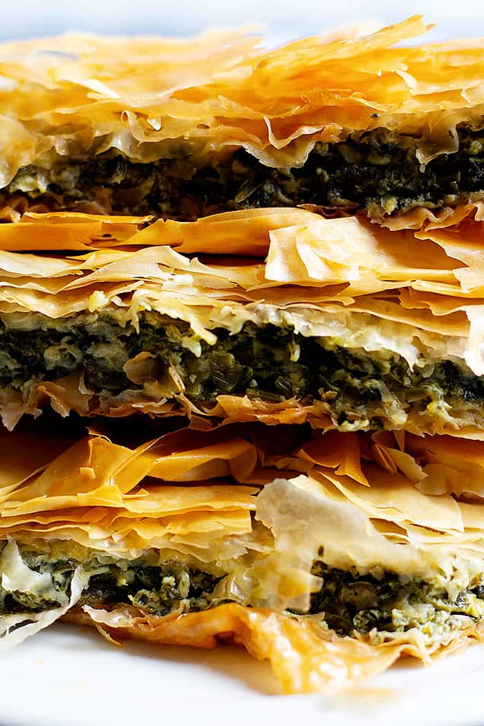 Spanakopita is a classic Greek pie made with phyllo dough, spinach and feta. It's packed with so much flavor and one slice is never enough! Learn how to make spanakopita recipe with a video tutorial.