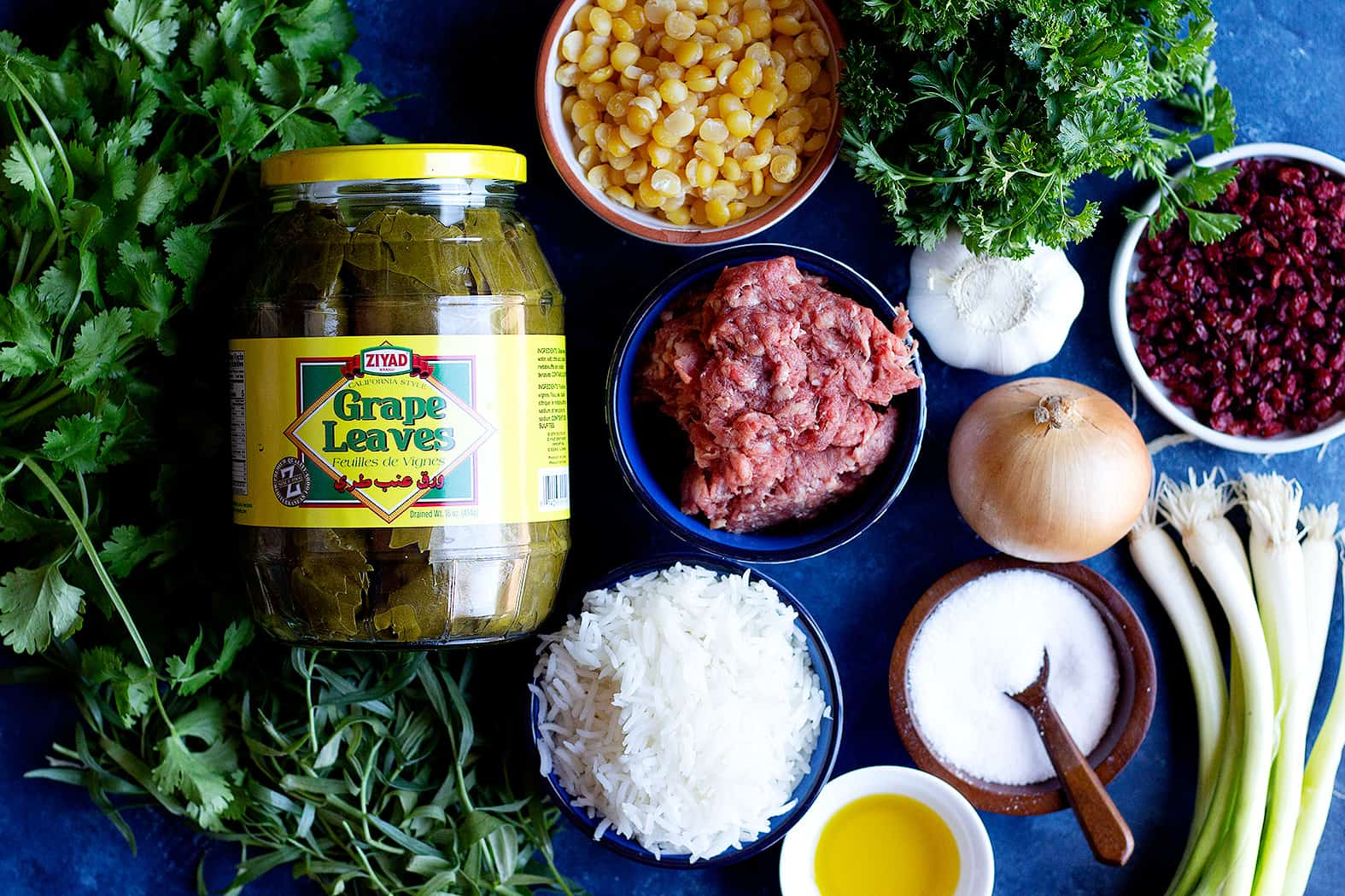 Ingredients to make Persian dolmeh recipe are grape leaves, rice, meat, onion, chana dal, onion, herbs and barberries.