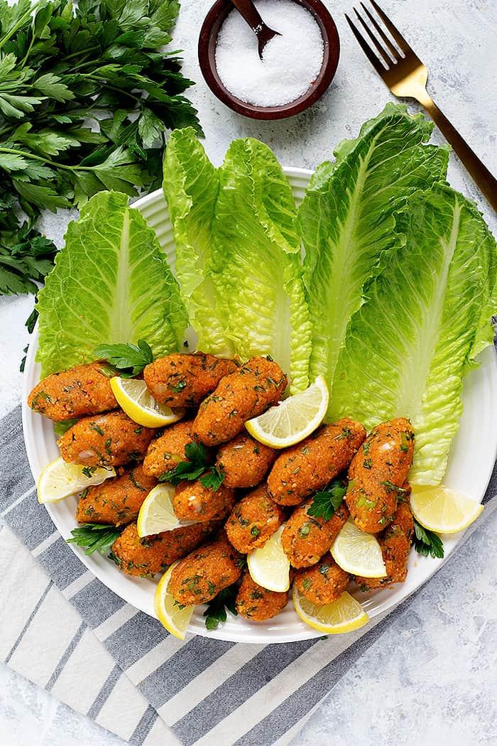 Turkish vegan red lentil balls in a platter with fresh lettuce and lemon slices.