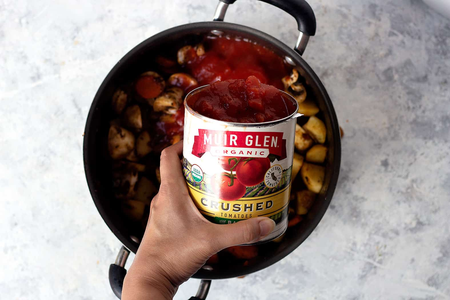 Pour a can of tomatoes into the beef and potato mixture to make the stew.