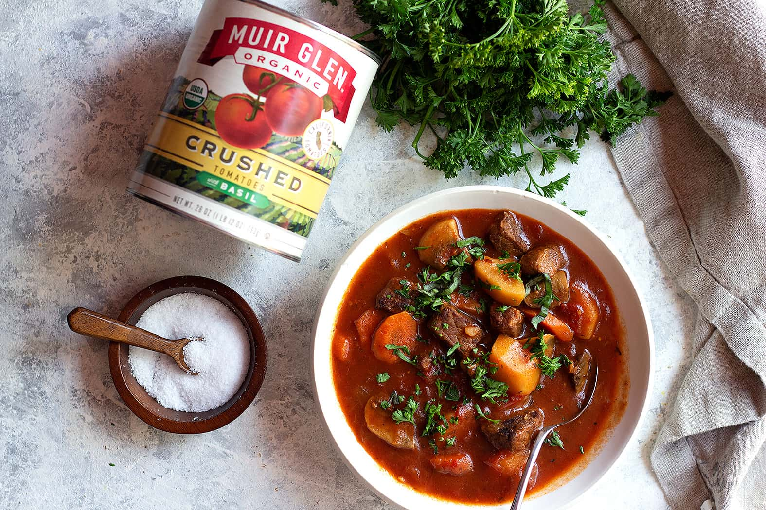 a bowl of beef stew with a can of tomatoes.