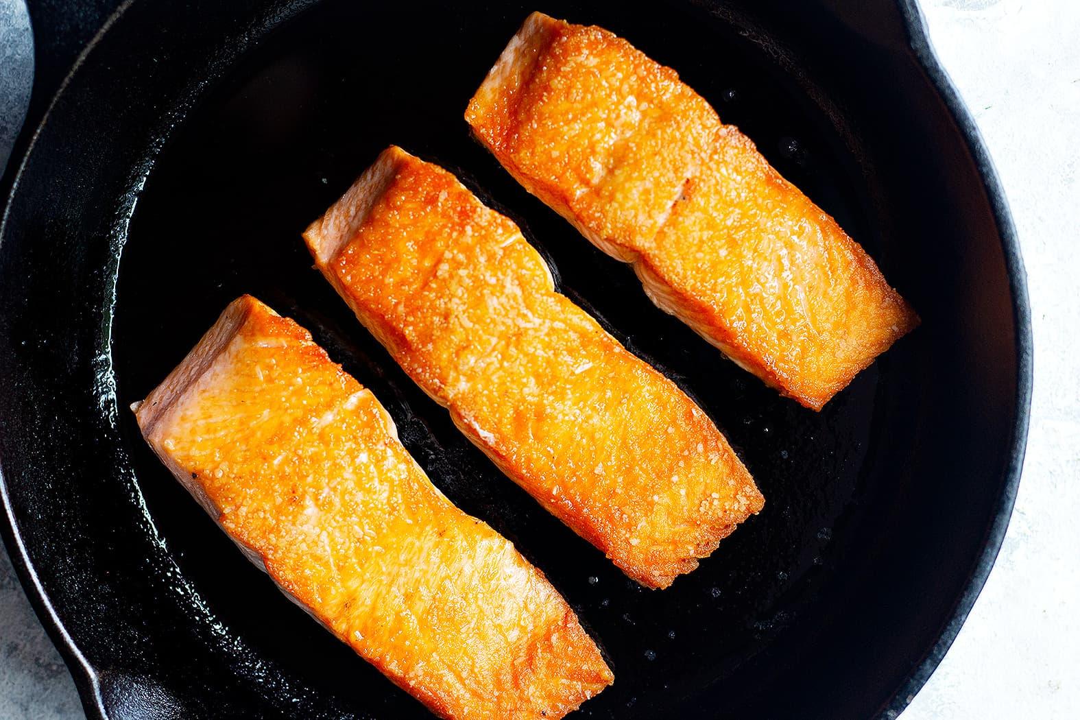 crispy salmon fillets in a pan to make orange glazed salmon recipe.