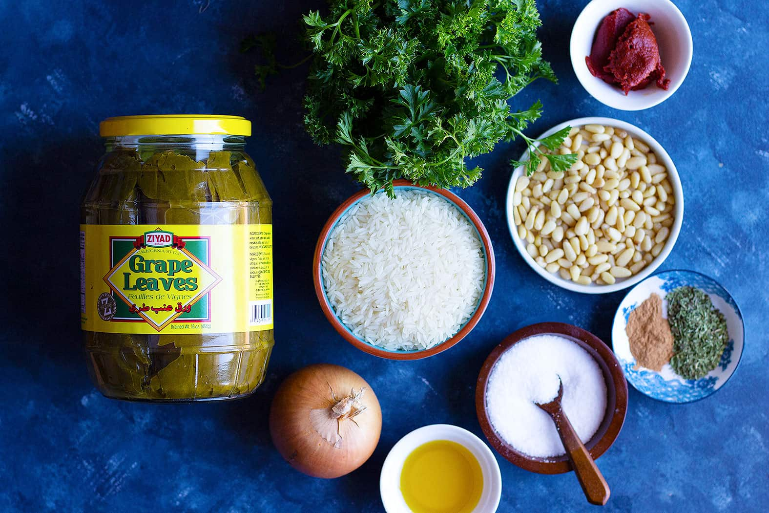 Ingredients shot for dolma recipe includes grape leaves, rice, onion, olive oil, parsley, spices, pine nuts and tomato paste