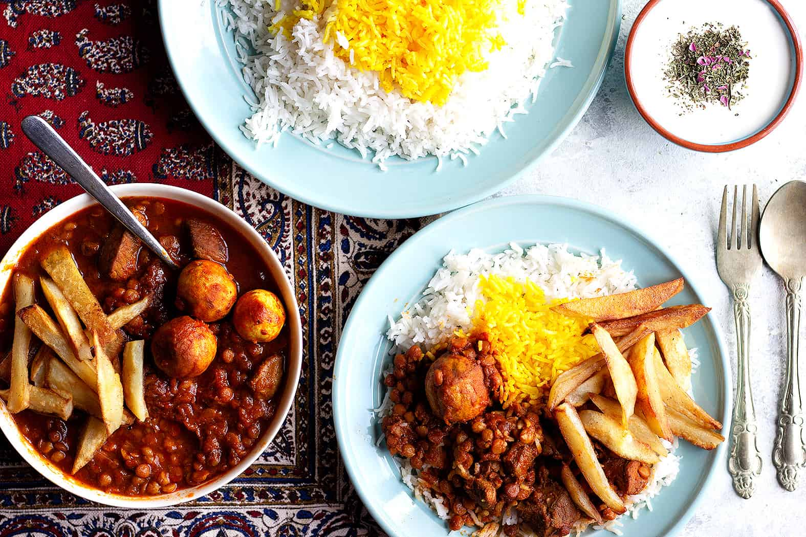 twp plates of rice serve with Persian gheimeh stew.