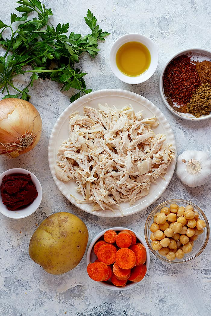 Ingredients to make this soup are olive oil. onion, garlic, carrots, potatoes, shredded chicken and spices.