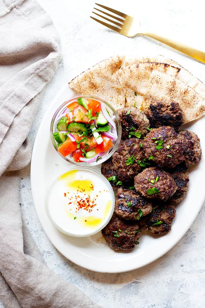 A platter of Turkish kofte kebab with sides and yogurt sauce.