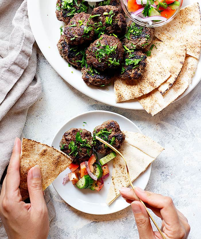 A plate of kofta kebab with pita and vegetables with a hand that's making a bite.