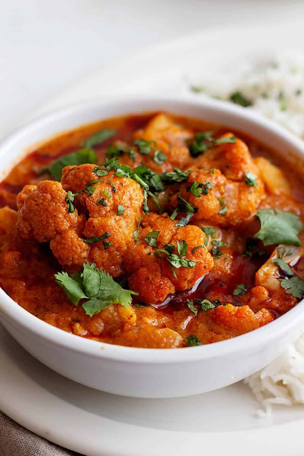 """Here's a delicious """"clean-the-fridge"""" vegetable tikka masala recipe that you'll love. Learn how to make a tasty vegetarian tikka masala with just a few ingredients and an easy shortcut. This cauliflower tikka masala is full of flavor and will knock your socks off!"""