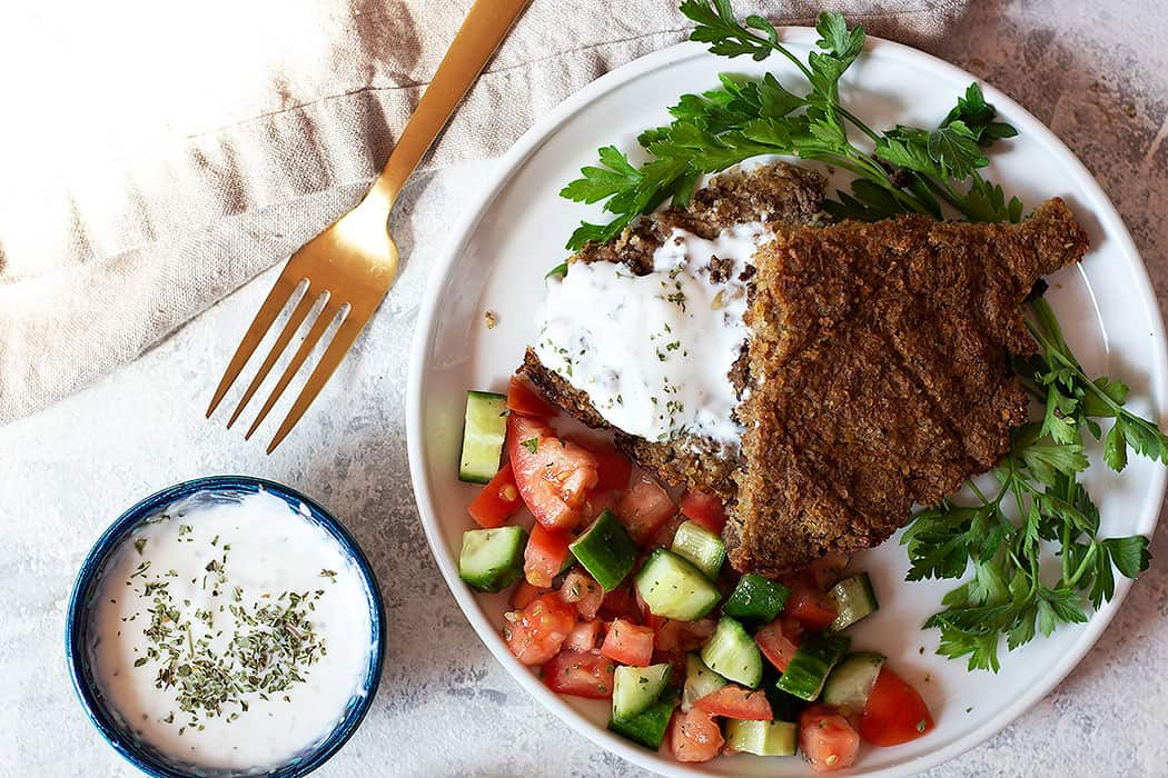 Baked middle eastern kibbeh with tomato cucumber salad and yogurt sauce.