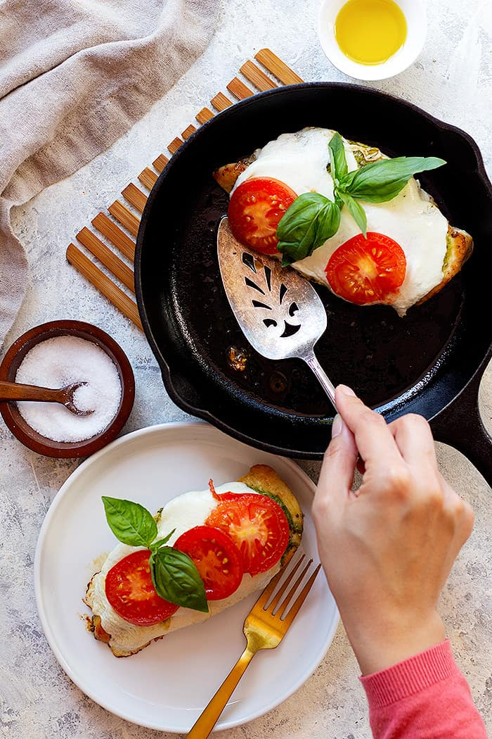 A pan of chicken caprese and a plate with pesto caprese chicken in it.