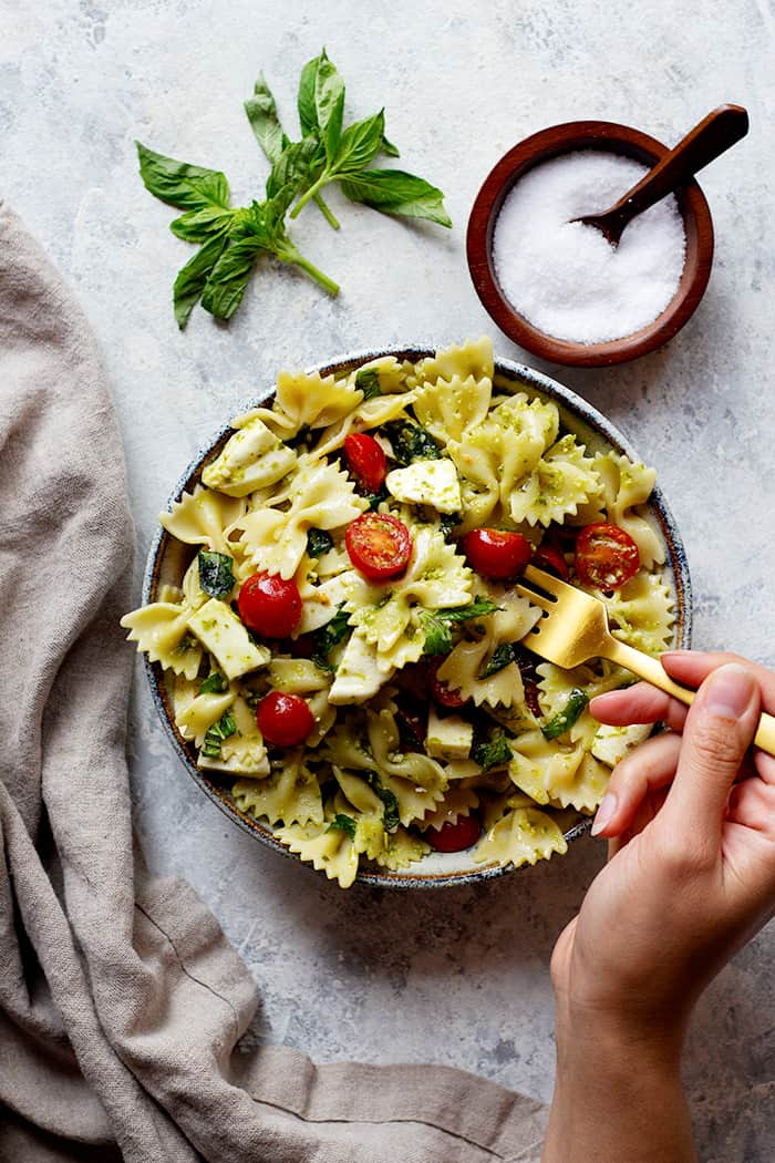 A bowl of pasta salad on a white background with salt and basil.