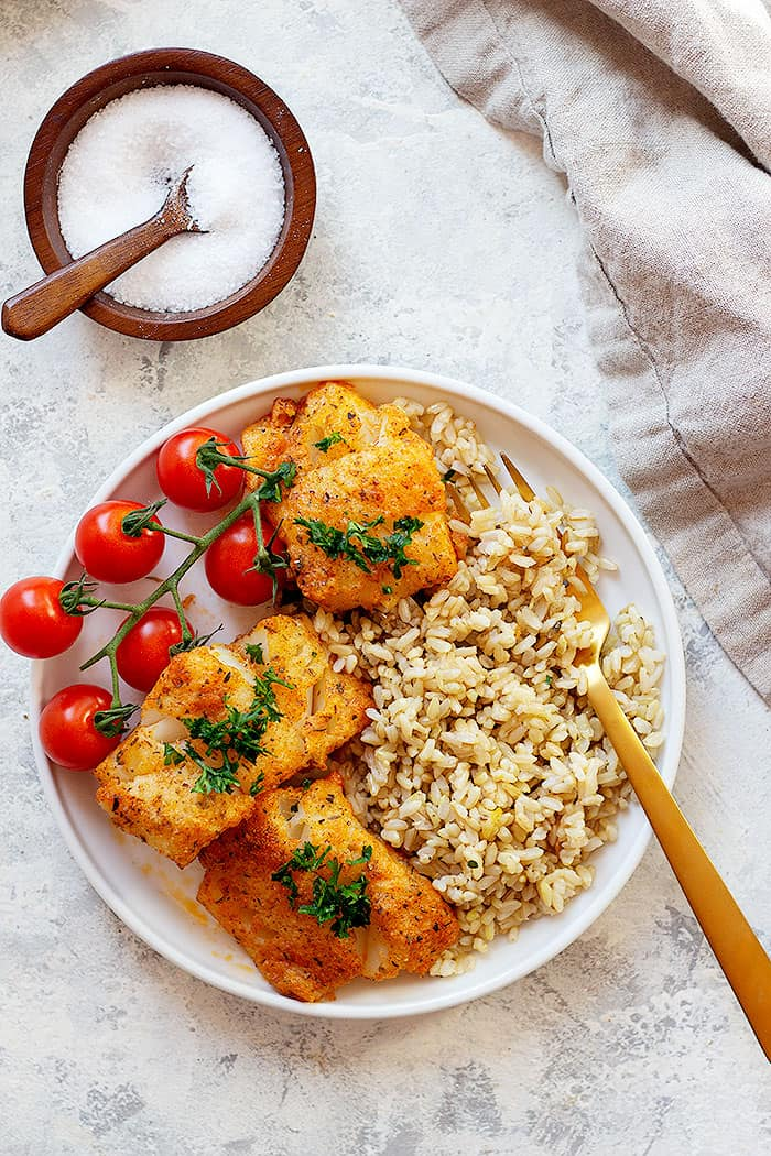 A plate of baked cod with rice makes a healthy dinner that you can make in less than 30 minutes.