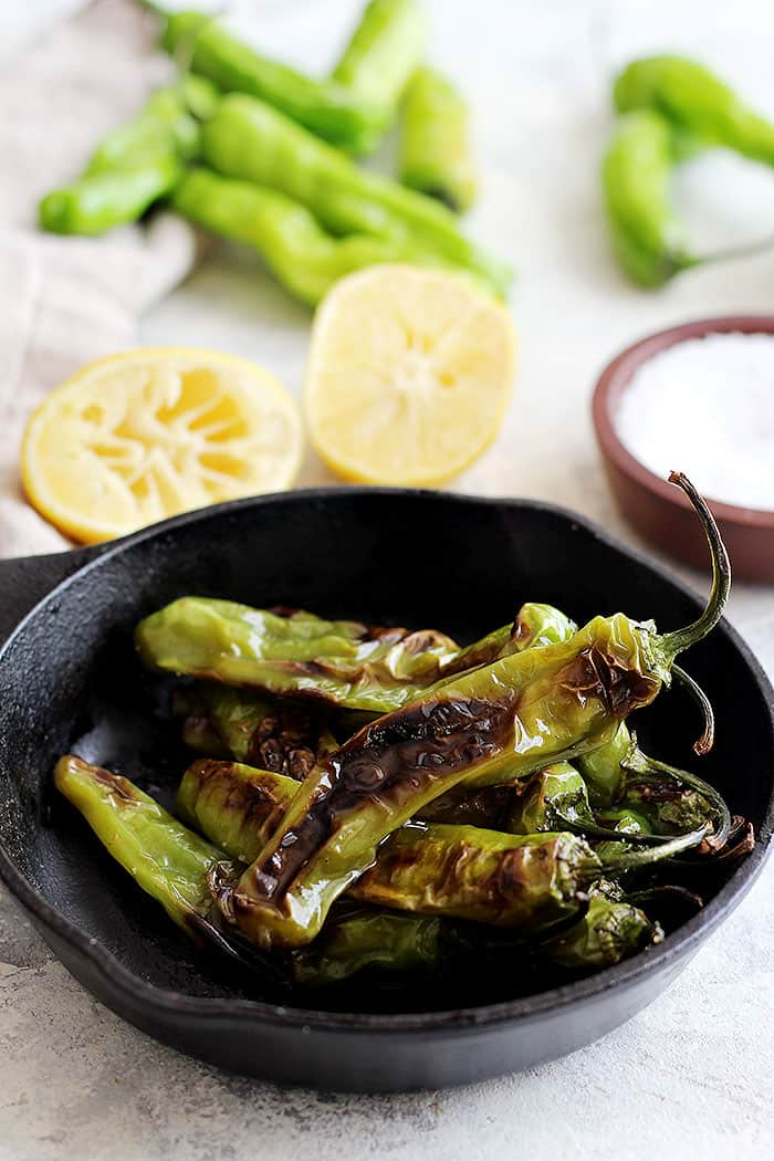Shishito peppers are sauteed and blistered in a cast iron skillet and served with a drizzle of lemon juice.