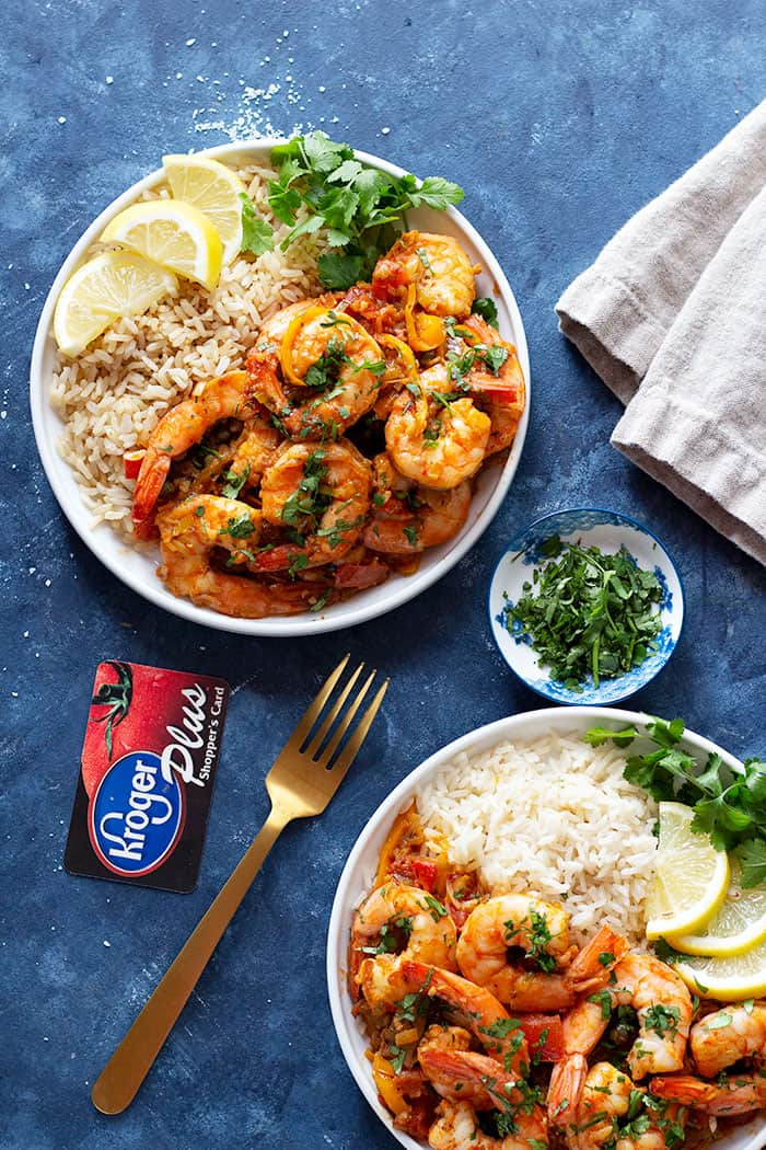 Two plates of shrimp and rice topped with lemon and parsley.