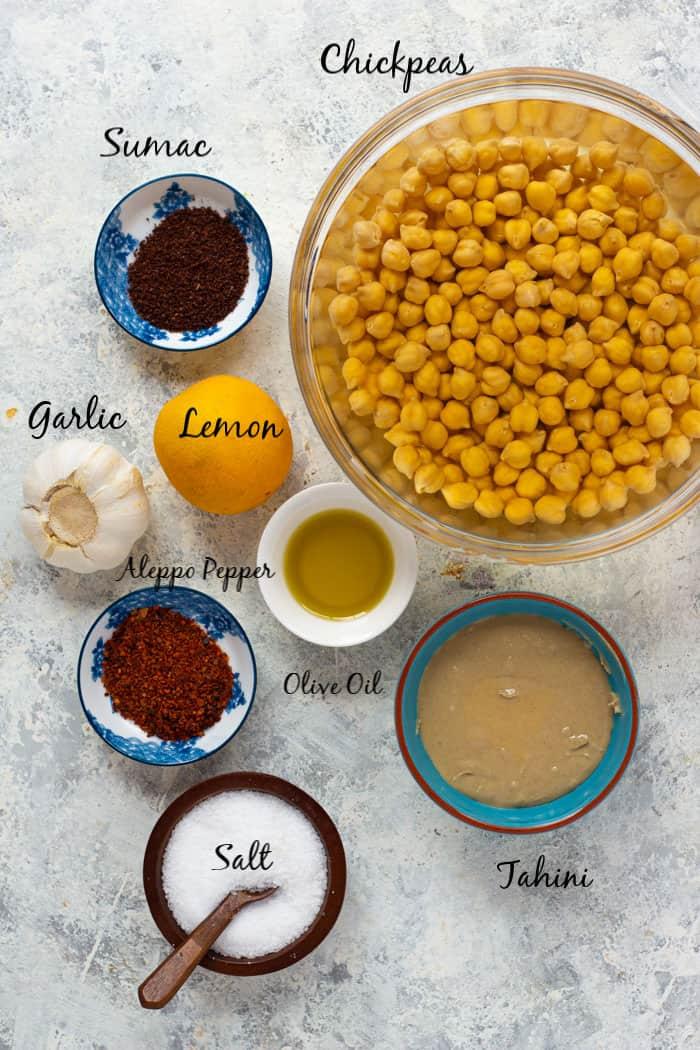 To make homemade hummus, you need chickpeas, sumac, lemon, garlic, tahini, olive oil, Aleppo pepper and salt.