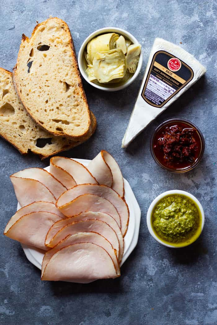 To make this dish, you need bread, pesto, roasted turkey breast, sun dried tomatoes, brie and artichokes.