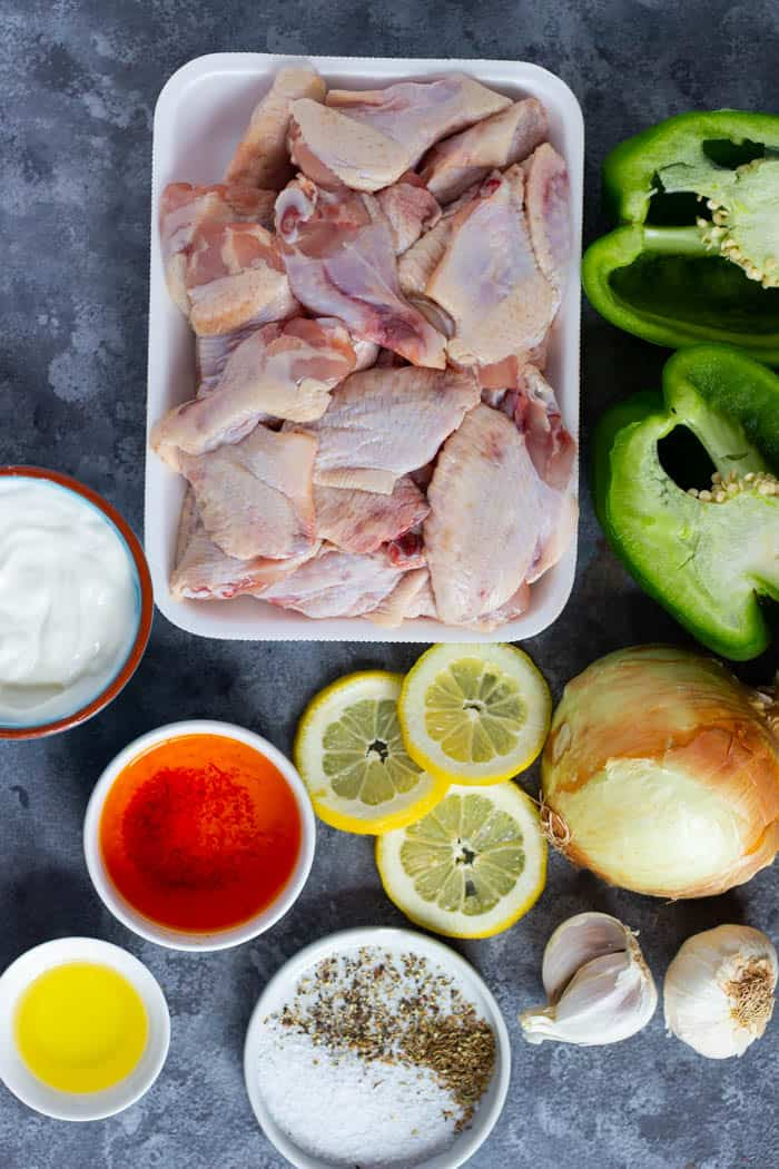 To make this recipe you need chicken wings, yogurt, saffron, lemon, onion, green bell pepper, olive oil, salt, pepper and garlic.