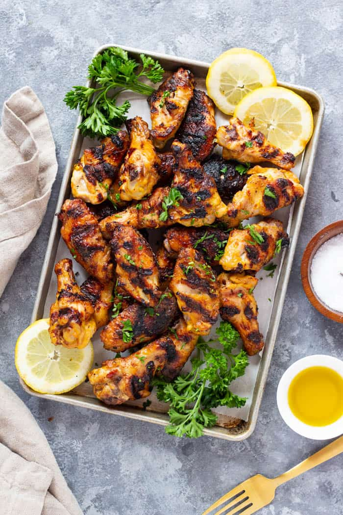 Chicken wings are grilled Persian style. Placed on a tray with sliced lemon and parsley.