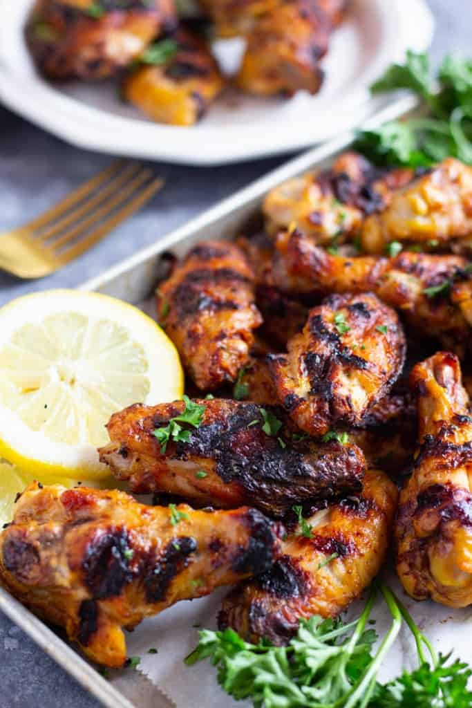 Persian style grilled wings on a tray with lemon and herbs.