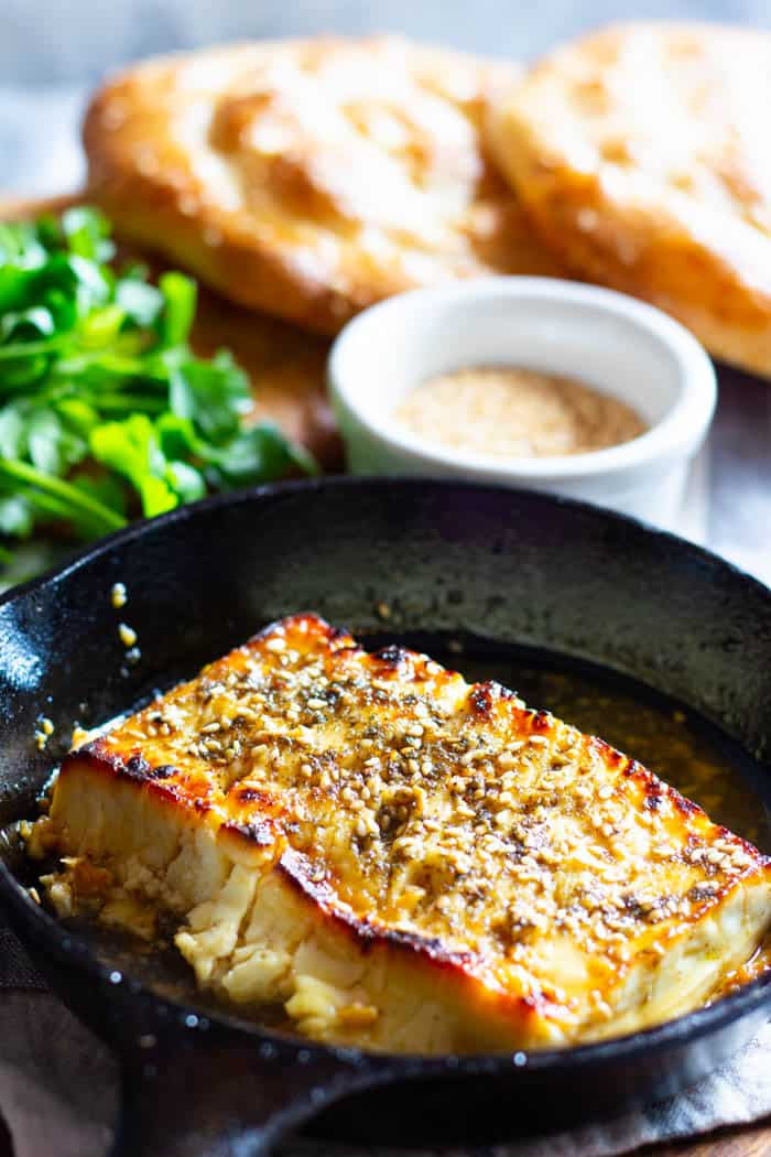 Baked feta in a cast iron skillet topped with honey and zaatar.