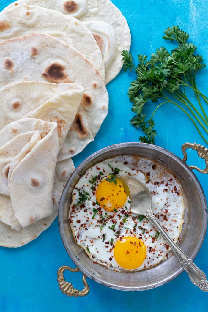 A pan of fried eggs and homemade lavash bread.