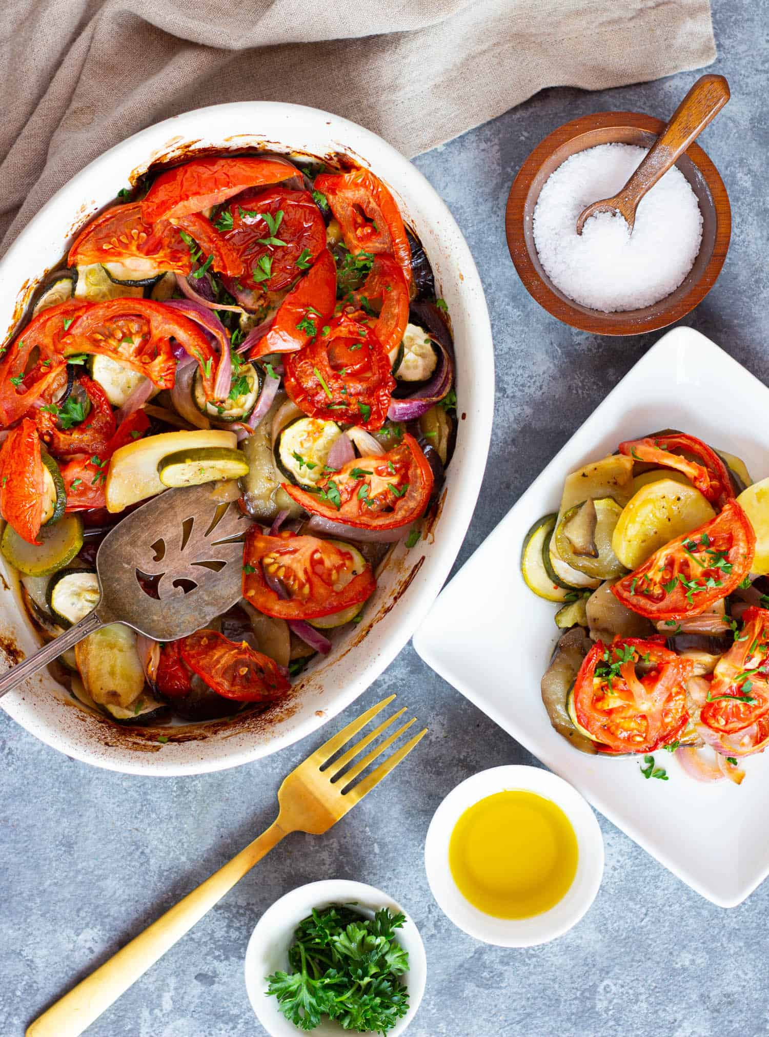A dish of Greek roasted vegetables and a serving plate filled with vegetables.