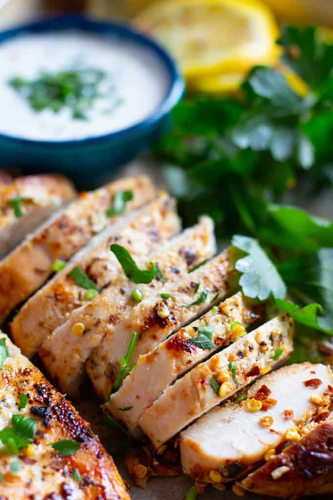 Close-up shot of juicy chicken breast cooked with Greek spices sliced into pieces.